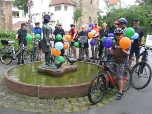 Radtourteilnehmer vor dem Aufbruch mit Ballons und Shirts