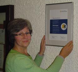 R. Stindl hängt die neue Gütesiegel-Urkunde im Rathaus auf